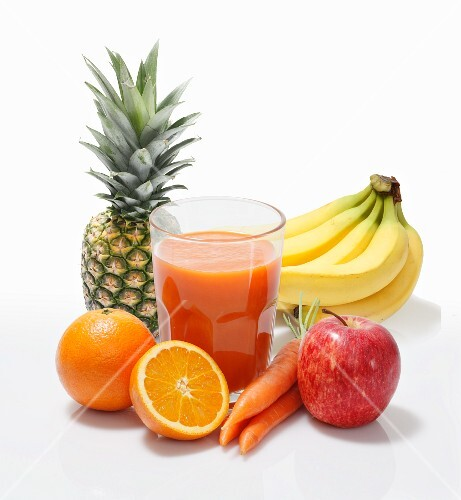 Multi-vitamin juice surrounded by whole fruits