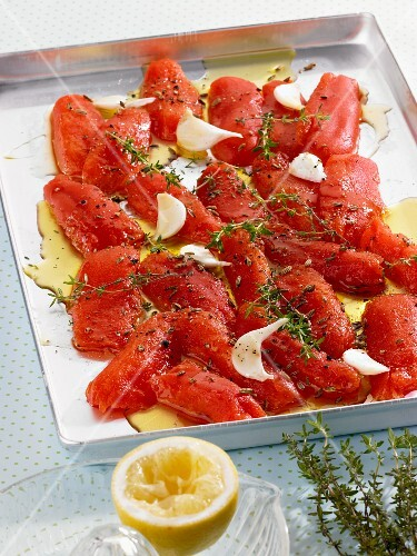 Tomatoes on a baking tray with thyme, garlic and olive oil