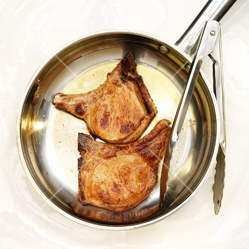 Two Seared Bone-In Pork Chops in a Skillet