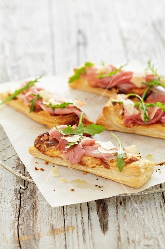 Puff pastry sticks topped with ham and rocket