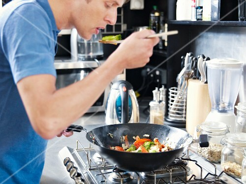 Man in kitchen cooking with wok