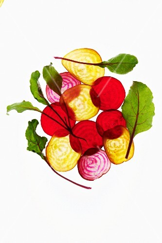 Thin Slices of Various Beets with Leaves on a White Background