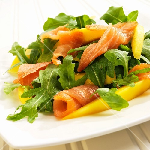 Arugula Salad with Salmon and Mango on a White Plate