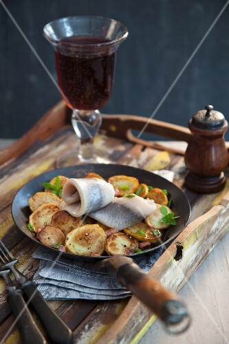 Soused herring with fried potatoes in a pan with a glass of red wine