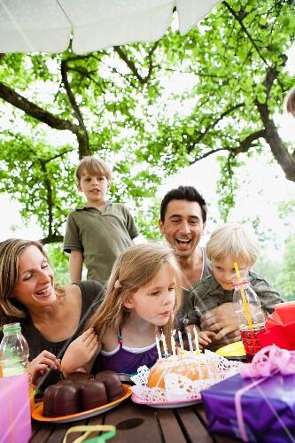 Family celebrating a birthday in garden