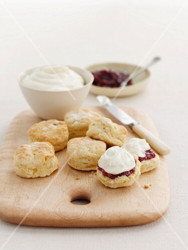 Scones with clotted cream and marmalade on a wooden board