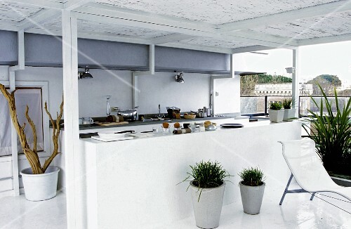 A white open plan kitchen on a covered terrace