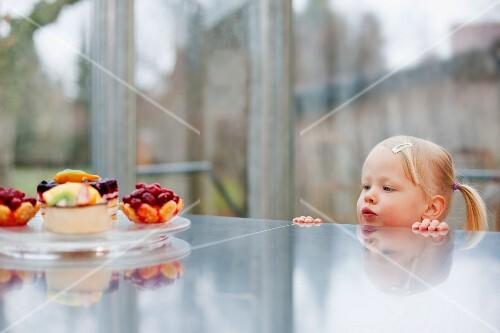 Toddler girl admiring fruit cakes