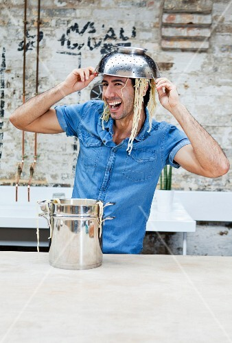 Man playing with spaghetti in kitchen