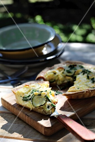 Courgette and leek quiche on a chopping board