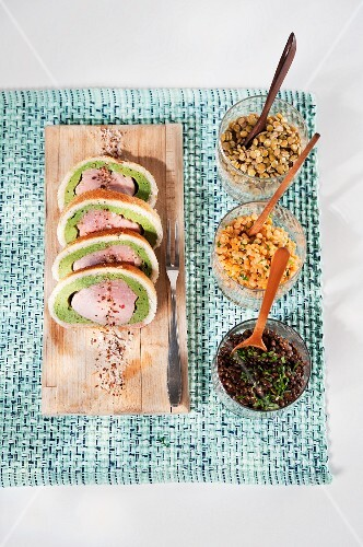 Pork fillet wrapped in bread and herbs on a bed of colourful lentils