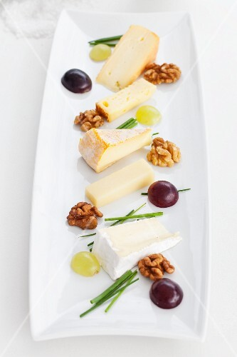 A plate of cheese specialities with walnuts, chives and grapes