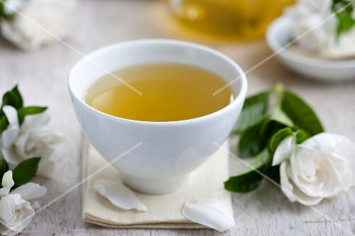 A tea bowl of green tea, surrounded by gardenia flowers
