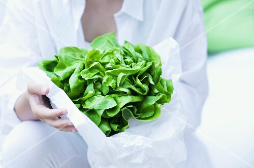 A girl holding a lettuce wrapped in paper