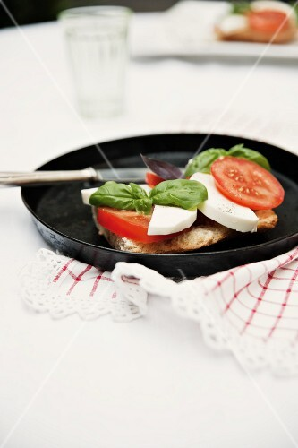 Bread topped with tomatoes, mozzarella and basil