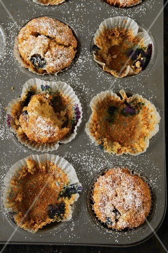 A half eaten tray of muffins