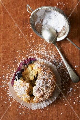 A fresh blueberry muffin with a bite taken out