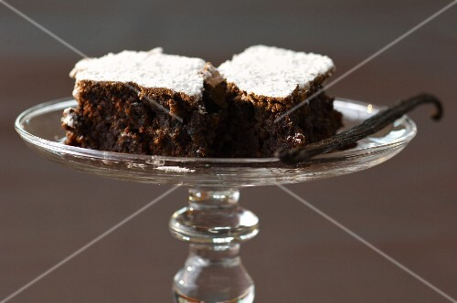 A vanilla pod and chocolate cake topped with icing sugar