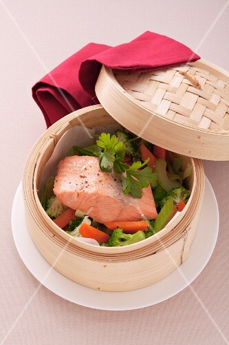 Steamed salmon with vegetables in a bamboo basket