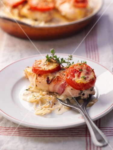 Chicken breast wrapped in bacon with tomatoes and thyme
