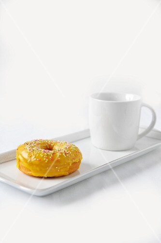 A doughnut with yellow glaze and sugar balls and a cup