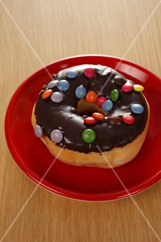 A doughnut with chocolate glaze and colourful chocolate beans