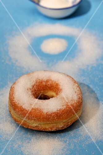A doughnut sprinkled with sugar on a blue surface