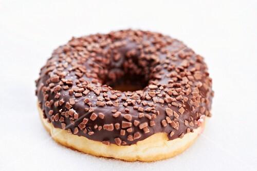 A doughnut with chocolate glaze and chocolate sprinkles