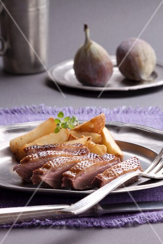 Duck breast with roast potatoes and fresh figs in the background