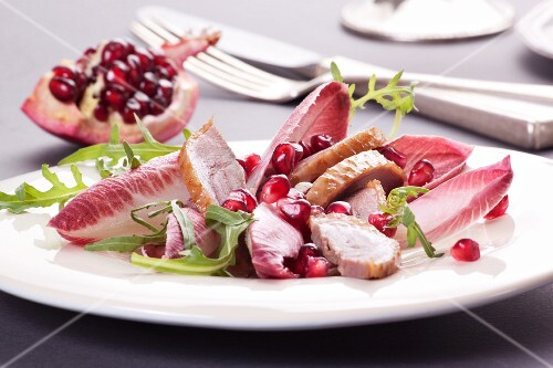 Goose breast with pomegranate seeds on a radicchio salad