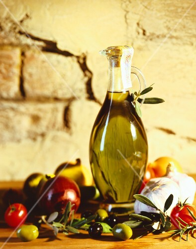 A carafe of olive oil with olives and tomatoes