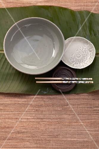 Bowls, plates and chopsticks on a banana leaf (Asia)
