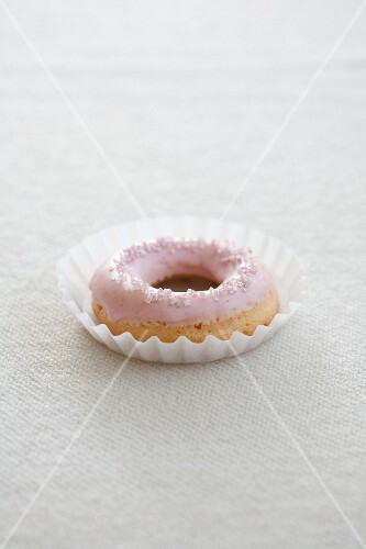 A doughnut with pink icing sugar