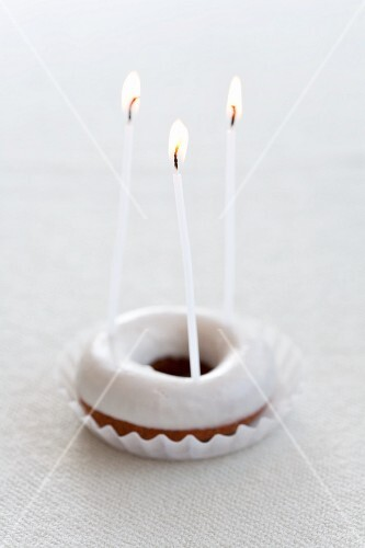 A doughnut with icing sugar and three candles