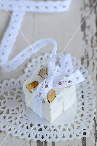 A cube of nougat decorated with a lace ribbon