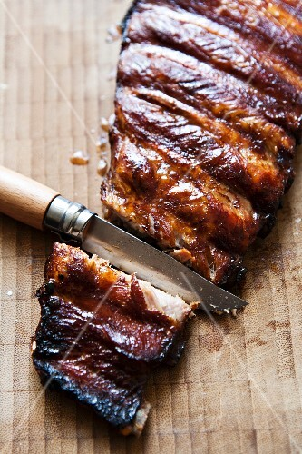 Spare ribs being separated on a wooden surface