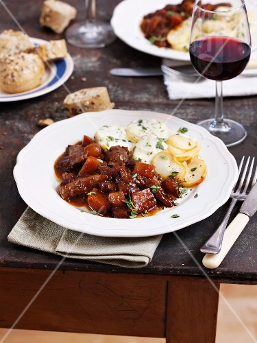 Boeuf Bourguignon with potato gratin and a glass of red wine