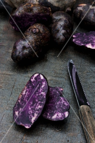 Vitelotte potatoes on a wooden board with a knife