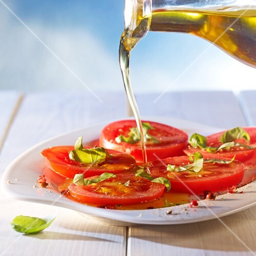 Olive oil being poured over seasoned tomato slices