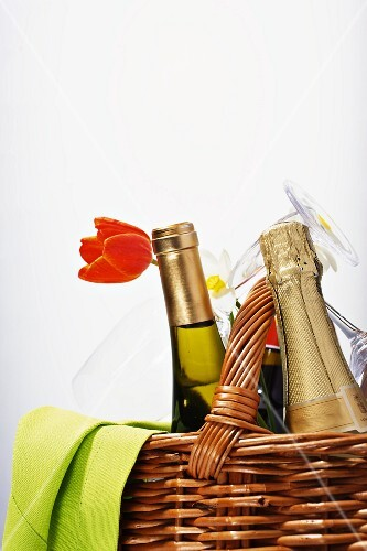 A bottle of champagne and a bottle of wine in a picnic basket with glasses