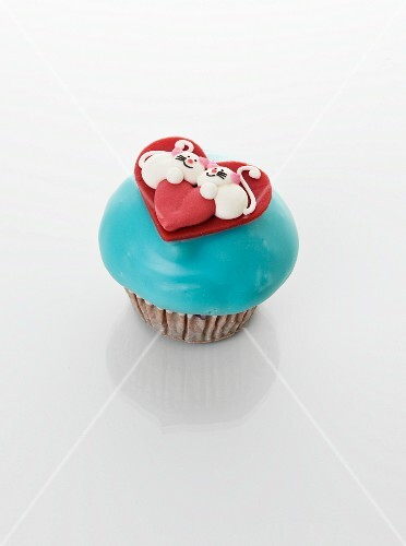 A cupcake decorated with couple of cats and a heart