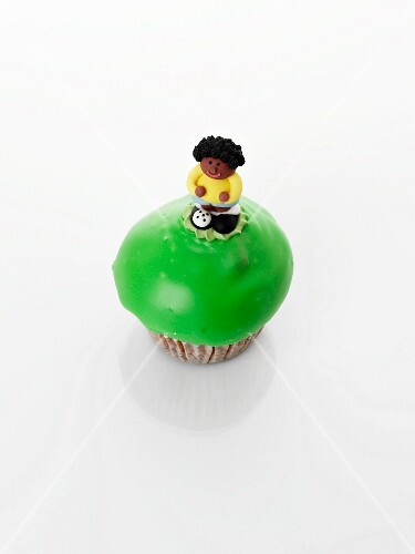 A cupcake decorated with a sugar figure