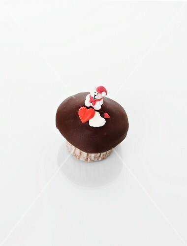 A cupcake decorated with a teddy bear and hearts