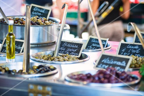Various types of preserved olives on a market stand