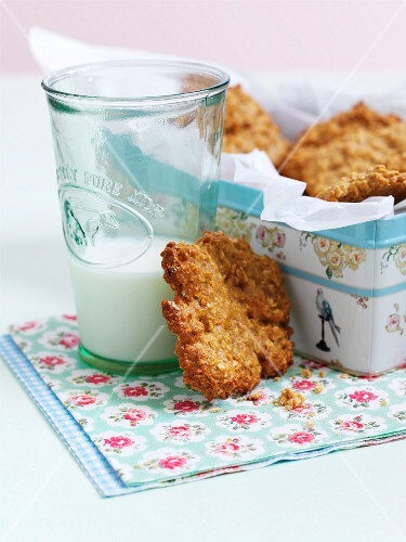 Oat and honey biscuits in a biscuit in with a glass of milk