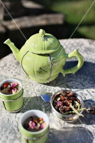 A lime-green teapot with silver dragonfly motif and matching tea tumblers on an antique garden table