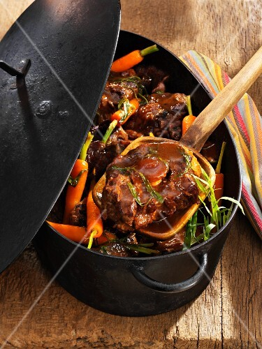 Oxtail ragout with carrots in a stewing pot