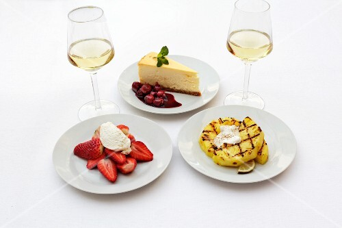 Cheesecake, strawberries and grilled pineapple with glasses of wine