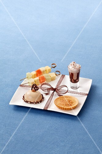 A dessert platter with fruit kebabs, a petit four, a tartlet and chocolate cream