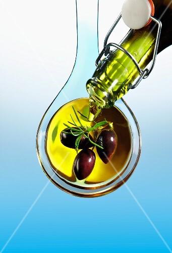 Olive oil being poured over olives